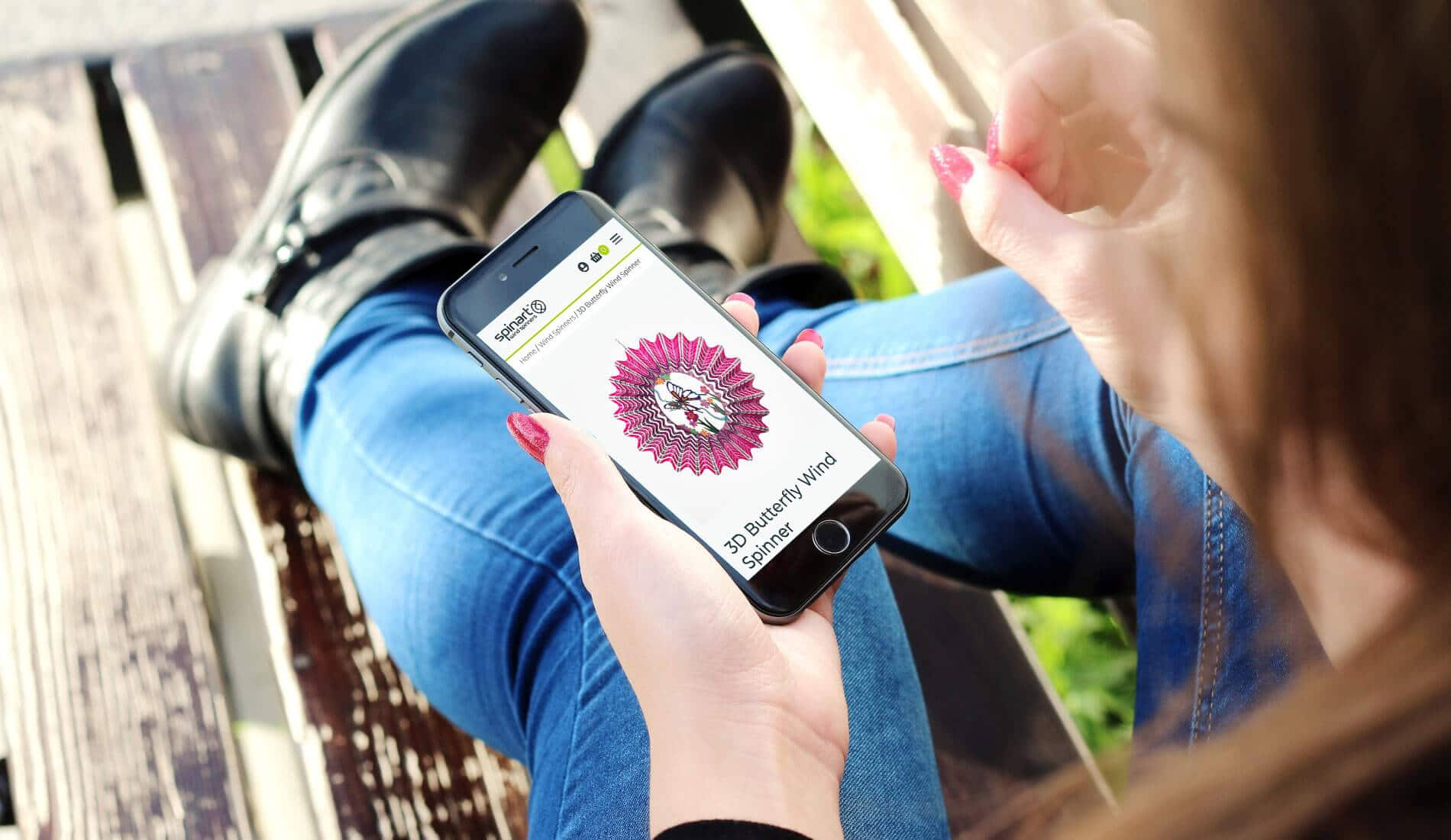 Girl on iphone looking at Spin Art Website