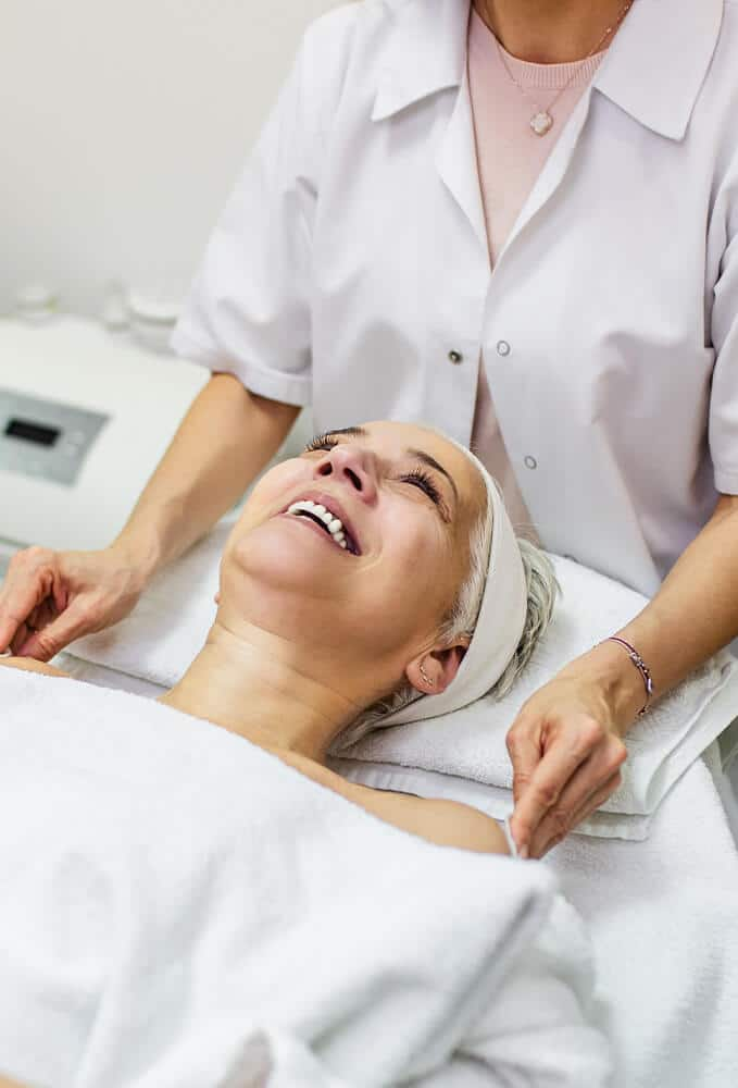 Skin Deep Rejuvenation woman laying on white bed for skin treatment